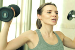 Young fit woman exercising with dumbbels in the gym NTSC Stock Footage