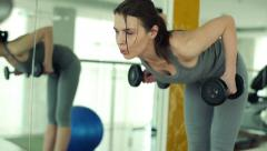 Young fit woman exercising with dumbbels in the gym HD Stock Footage