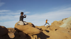 Medium shot of woman photographing man jumping on rock in Goblin Valley / Goblin Stock Footage