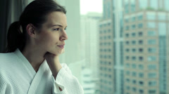 Pensive woman looking through the window at city HD - stock footage