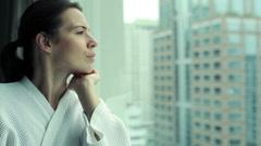 Mietteliäs nainen etsii läpi ikkunasta kaupungin HD Arkistovideo