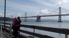 Two girls on the waterfront of San Francisco bay opposite Oakland Bay Bridge. Stock Footage