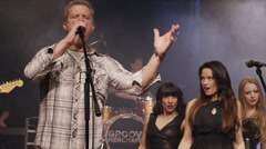 Performer singing on stage with backup singers / Spanish Fork, Utah, United Stock Footage