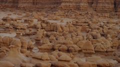 Panning medium shot of rock formations in Goblin Valley State Park / Goblin - stock footage