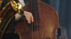 Close up rack focus shot of man playing cello on stage / Provo, Utah, United Stock Footage
