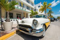 vintage car parked at ocean drive in south beach, miami - stock photo