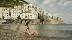 WS Young woman relaxing on Amalfi Beach / Italy Stock Footage