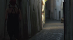 Stock Video Footage of WS Rear view jogging in narrow street of narrow town at dusk / Ravello,Italy
