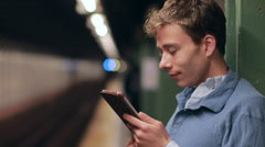 Young Caucasian man in city subway station using tablet pc Stock Footage
