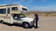 Man Cooling Vehicle Radiator Of RV Camper In Hot Desert Stock Footage