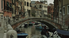 WS People in motorboat swimming under small arch bridge in old town / - stock footage