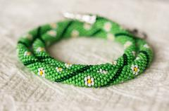 Necklace from beads with flower drawing on a textile background Stock Photos