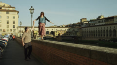 MS Man assisting woman walking on top of waterfront ledge with Ponte Vecchio in Stock Footage