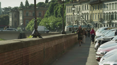 WS Man jogging along ledge by river Arno / Florence,Tuscany,Italy Stock Footage