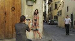WS Man taking photographs of woman on old towns street / Florence,Tuscany,Italy Stock Footage