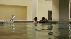 WS Couple talking in indoor swimming pool / Petriolo,Marche,Italy Stock Footage
