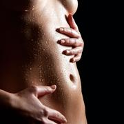 Wet belly of a nude slim woman Stock Photos