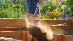 Man putting dry soil in raised garden bed with shovel in garden. Slow motion. Stock Footage
