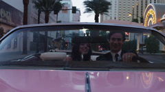 POV MS Couple driving through neon illuminated city street in convertible car / Stock Footage