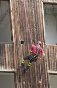 brave fireman you haul in the wall of the house abseiling during an exercise - stock photo