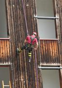 Expert firefighter down into the wall of the house in abseiling Stock Photos