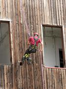 brave fireman climber expert you haul in the wall of the house abseiling - stock photo