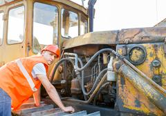 working  examining bulldozer engine - stock photo