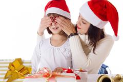 Mother covering daughter eyes with hands hiding Christmas gifts Stock Photos