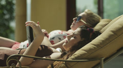 MS Two girls (14-19) at poolside using tablet pc / Cedar Hills, Utah, USA Stock Footage