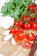 Fresh tomatoes, rucola and garlic Stock Photos