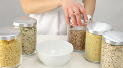 Female hands holding a pot with raw buckwheat Stock Footage