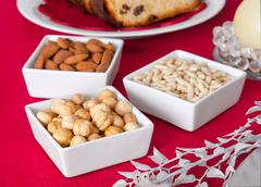 Pine nuts, almonds and hazelnuts in bowls on the Christmas table Stock Photos