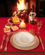 Christmas table near the fireplace, set for a single person. - stock photo