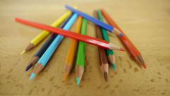 Colored pencils on a wooden table - camera move. Stock Footage