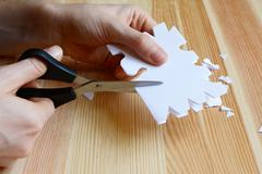 Using scissors to cut out a paper snowflake shape - stock photo