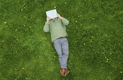 A man lying on his back on the grass, reading a book. Stock Photos