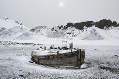 A wooden boat hull beached on deception island, a former whaling station. Stock Photos