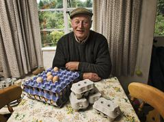 A farmer seated at a table in a farmhouse with trays of fresh eggs. Stock Photos