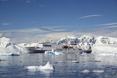 an antarctic cruise ship with inflatable zodiacs on the calm waters among ice - stock photo