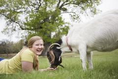 A girl lying on grass head to head with a goat. Stock Photos
