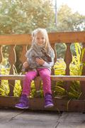 Smiling little girl posing in arbor with rabbit - stock photo
