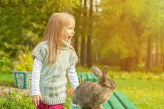 Cheerful little girl walking with rabbit in park Stock Photos
