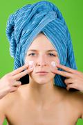 woman in blue towel applying facial cream - stock photo