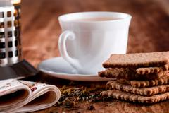 french press, cup of fresh herbal tea and some cookies - stock photo