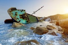 shipwreck and seascape sunset - stock photo