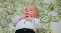 Rich child, little baby kid toddler among many money U.S.dollars Footage