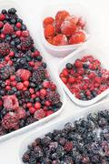 Plastic containers of frozen mixed berries in snow - red currant, cranberry, ras - stock photo