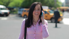 Young Latina Hispanic woman in city walking talking smart phone cellphone - stock footage