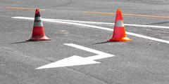 Road block with white arrow showing the alternate way Stock Photos