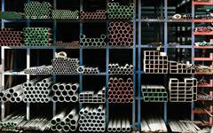 Pipes stacked up in a factory Stock Photos